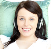 Young woman listening music lying on a sofa Royalty Free Stock Photos