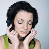 Young woman listening music. Portrait of a young woman listening music on  background Royalty Free Stock Image
