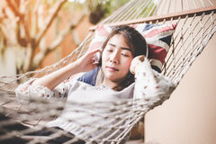 Young woman listening music relax lying in a hammock in the holiday Stock Photo