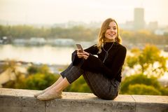 Young woman listening music from smartphone outdoor at sunset Stock Images