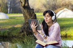 Young woman listening music from a tablet in an autumn park. Beautiful woman reading a book in an autumn park stock photos