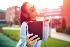 Young woman listening music on tablet by headphones. Enjoying and laughing in sunset. Singing and dancing outdoor Stock Photo