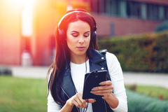 Young woman listening music on tablet by headphones in sunset. Outdoor Stock Photography