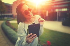 Young woman listening music by tablet and headphones in sunset. Outdoors Royalty Free Stock Images
