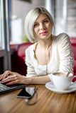 Young Woman Listening Music While Working On Laptop In Cafe Royalty Free Stock Photo
