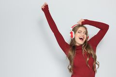 Young woman listening to Christmas music. On color background royalty free stock photography