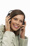 Young woman listening to earphones, cut out Royalty Free Stock Photography