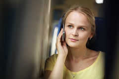 Young woman listening to her mobile while travelling by train Royalty Free Stock Images