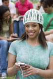 Young woman listening to MP3 player, smiling, focus on foreground Stock Image