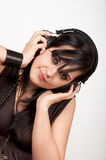 Young woman listening to the music. Beautiful young woman wearing headphones and listening to the music. Studio shot Stock Image