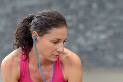 Young woman listening to music as she exercises. Young woman listening to music on earbuds as she exercises looking to the side with a serious preoccupied Royalty Free Stock Image