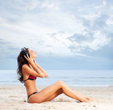 A young woman listening to the music on the beach Stock Image