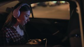 Woman passenger listening to music in a car in stereo headphones. Young woman listening to music in a car in stereo headphones sitting on passenger seat stock video footage