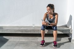 Fitness runner listening to music on mobile phone. Young woman listening to music with earphones on smart phone app for fitness motivation. Athlete runner in royalty free stock image