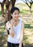 Young woman listening to music with earphones on smart phone app. In the park Stock Photo