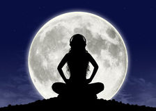 Young woman listening to the music at the full moon. Silhouette of a young beautiful woman with long hair in headphones in meditation posture with the full moon Royalty Free Stock Photos