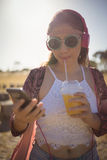 Young woman listening to music while having drink Stock Photo