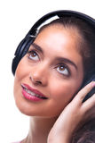 Young woman listening to music through headphones. Royalty Free Stock Photos