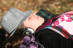 Young woman listening to music with headphones. Lying young woman listening to music with headphones wearing hat stock image