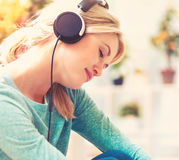 Young woman listening to music on headphones. Happy young woman listening to music on headphones at home Royalty Free Stock Photo
