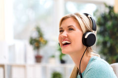 Young woman listening to music on headphones Stock Images