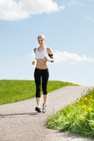 Young Woman Listening To Music On Headphones While Jogging Royalty Free Stock Photo