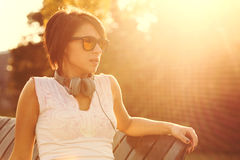 Young woman listening to music in headphones outside Stock Photography
