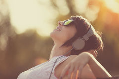 Young woman listening to music in headphones outside Royalty Free Stock Photos