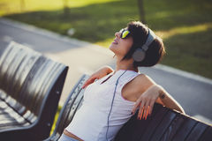 Young woman listening to music in headphones outside Stock Photo