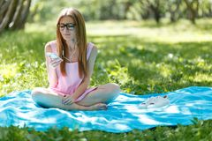 Young woman listening to music on headphones. Sits on the grass in the park, resting enjoys nature. stock photos