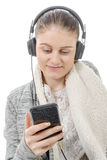 Young woman listening to music with his mobile phone and headph Stock Photography