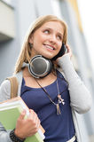 Young woman listening to music holding books Royalty Free Stock Photo