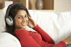 Young Woman Listening To Music At Home. Smiling Royalty Free Stock Photos