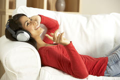 Young Woman Listening To Music At Home. Smiling Stock Photos