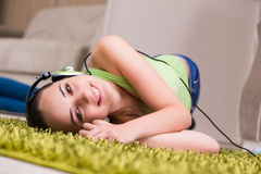The young woman listening to music at home Stock Images