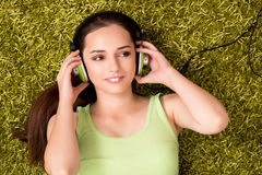 The young woman listening to music at home Stock Photos