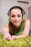 The young woman listening to music at home Stock Image