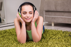The young woman listening to music at home Stock Photography