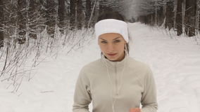 Young woman listening to music and jogging outside in winter