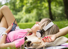 Young woman listening to music while laying down on grass Stock Images