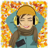 Young woman listening to music lying on autumn leaves floor. Young beautiful woman listening to music lying on autumn leaves floor Royalty Free Stock Photography
