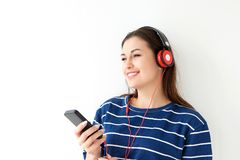 Young woman listening to music with mobile phone and headphones against white background. Close up portrait of smiling young woman listening to music with mobile Royalty Free Stock Photography