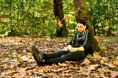 Young woman listening to music in nature. Girl in a park in autumn Stock Image