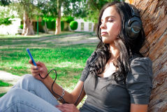 Young woman listening to music at a park Royalty Free Stock Photos