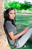 Young woman listening to music at a park Royalty Free Stock Photo