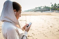 Young woman is listening to the music on the phone before joggin. G on the beach at the sunrise Royalty Free Stock Photography