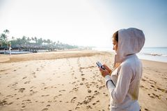 Young woman is listening to the music on the phone before joggin. G on the beach at the sunrise Stock Image