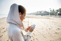 Young woman is listening to the music on the phone before joggin. G on the beach at the sunrise Royalty Free Stock Photo