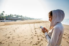 Young woman is listening to the music on the phone before joggin. G on the beach at the sunrise Stock Photo