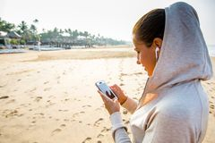 Young woman is listening to the music on the phone before joggin. G on the beach at the sunrise Royalty Free Stock Images